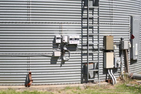 Grain bin fan control systems mounted on the side of a grain bin