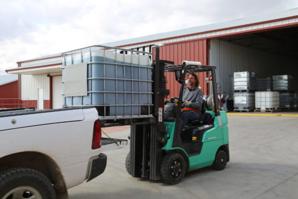 Hefty Seed Warehouse Employee loading up bulk chemical products